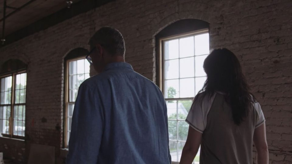 john and ashely marsh walk through a hall