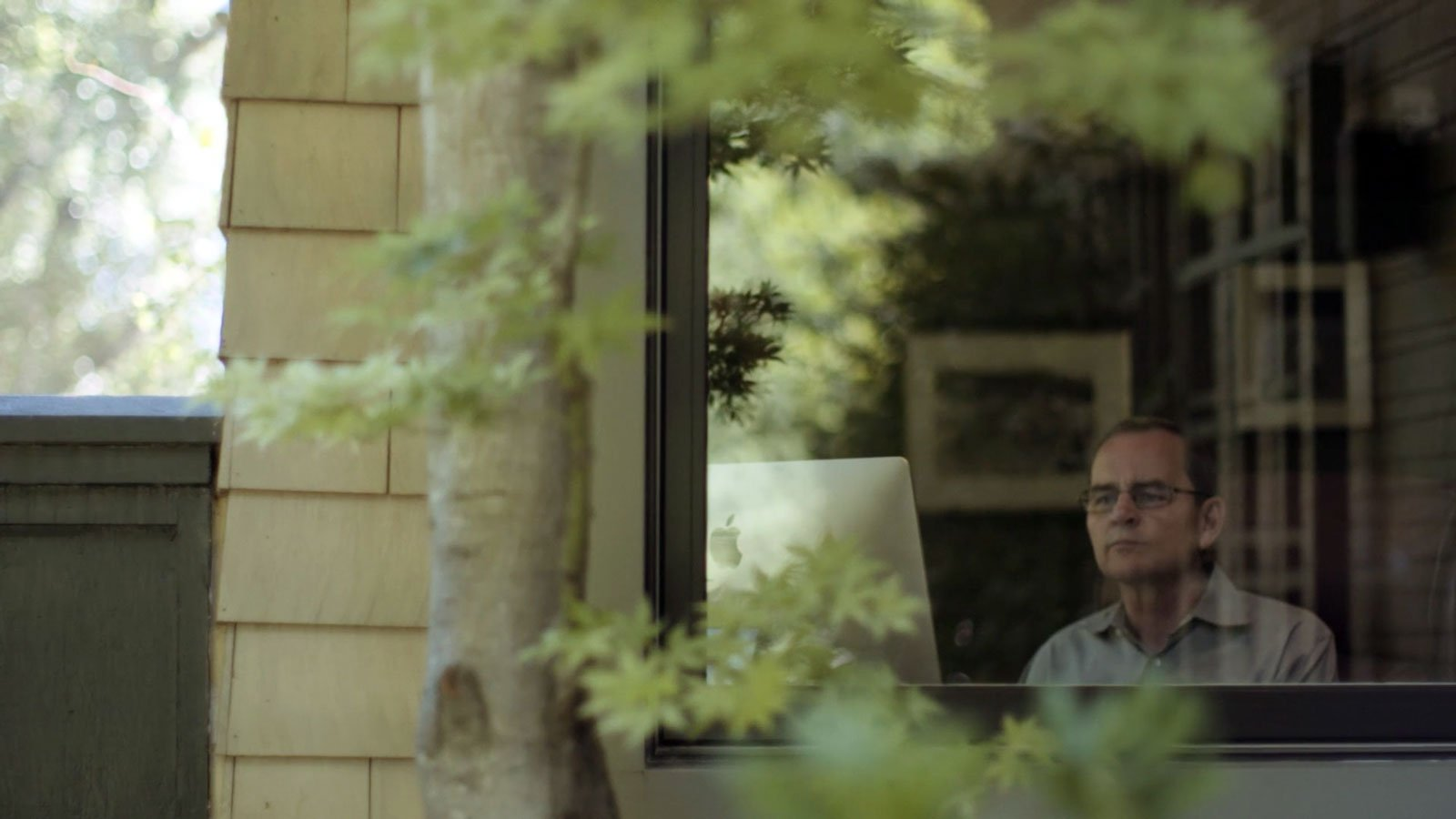 john brandon seen through a window as he's on his macbook